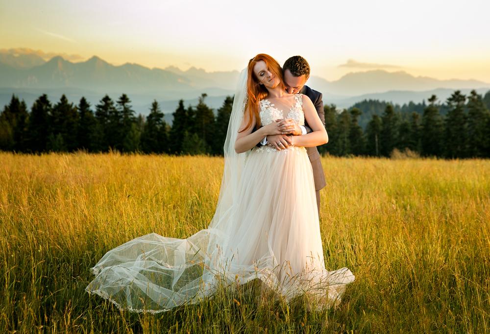 Obejmująca się Para Młoda na sesji ślubnej w Pieninach na łące