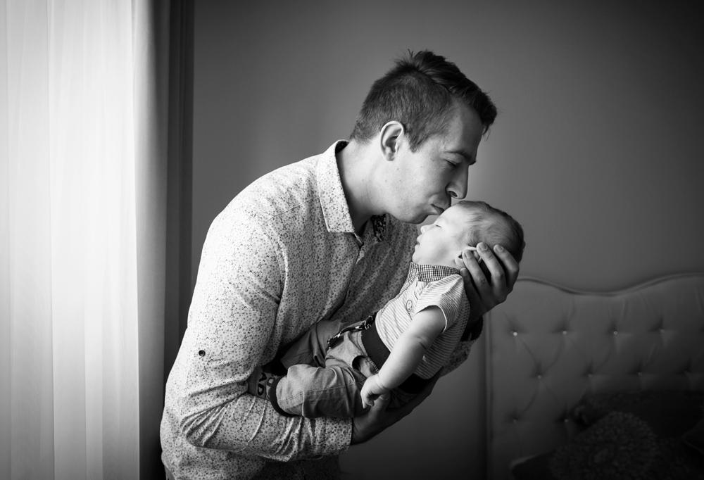 Ojciec trzymający na rękach swojego syna na sesji rodzinnej w domu