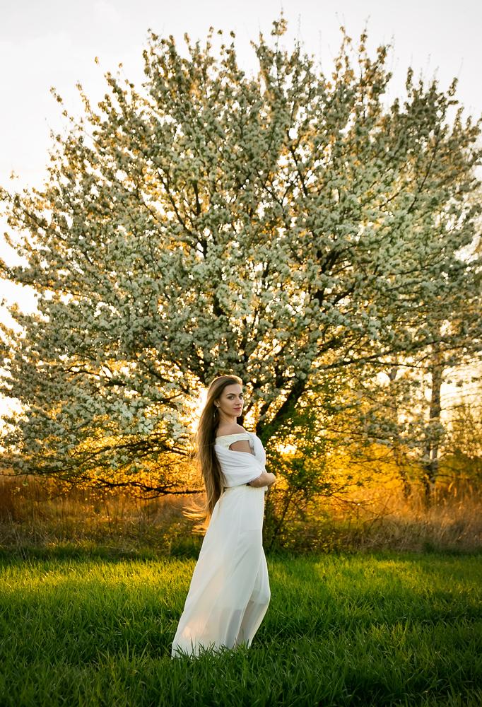 Piękna kobieta w białej sukience na łące podczas kobiecej sesji w plenerze o zachodzie słońca.