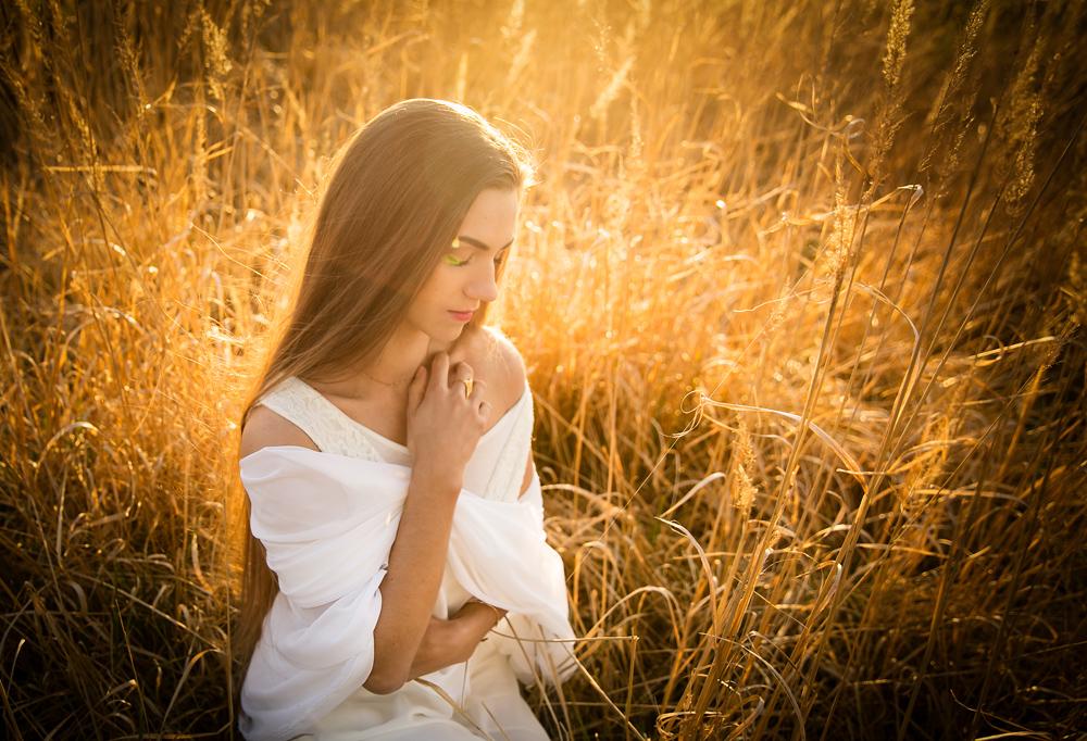 Kobieta o zachodzie słońca podczas sesji kobiecej w plenerze